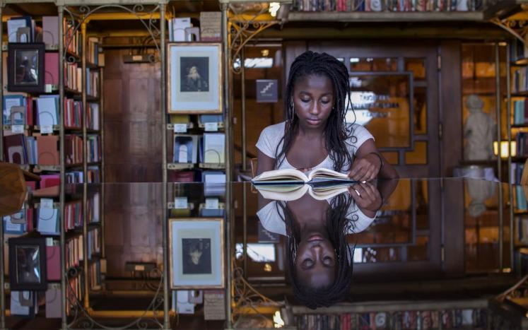 winning photograph of girl reading book in library with reflection